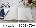 白いデスク上のノートとスマートフォンのフレーム 80934790