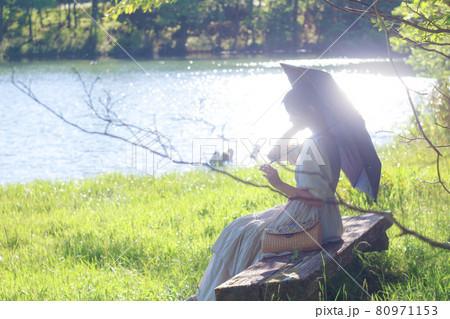 湖の近くに座る日傘をさしたワンピースの女性 80971153