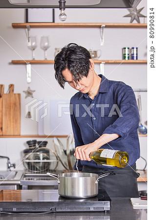 鍋にワインを注ぐエプロン姿の若い男性 料理男子イメージ 80990814