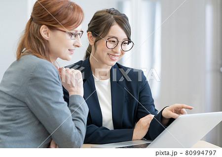 パソコンを見ながら会話する日本人と西洋人の若いメガネの女性2人 撮影協力:中央工学校付属日本語学校 80994797