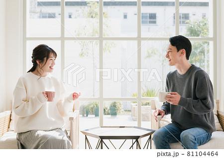 庭の見えるリビングでティータイムを楽しむ夫婦 81104464