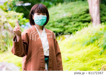 マスクをつけて温泉旅行をする浴衣姿の女性 81172367