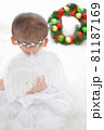 クリスマスリースを見つめる白い羽の赤ちゃん天使 81187169