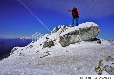 冬の空木岳山頂から御嶽山を指さす登山者 81252034