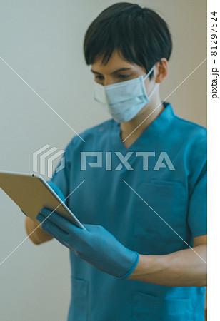 タブレット端末を操作する医療従事者 81297524