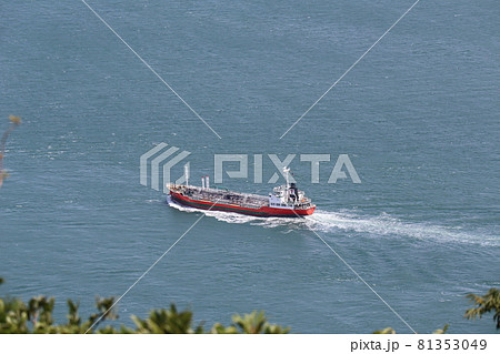 ぼやけて見える緑の葉の向こうにタンカーの行く青い海 81353049