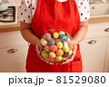 Woman in red apron holding glass bowl with sweets 81529080