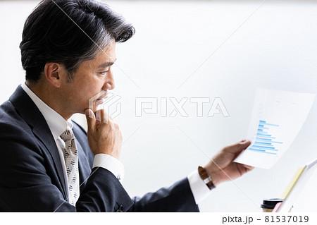 デスクワーク中に紙資料を見るビジネスマン 81537019