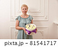 Woman confectioner holding box with sweets on white background 81541717