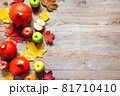 Autumn border from apples, pumpkin and fallen leaves on old wooden table. 81710410