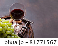 Red wine glass and white grape on old barrel 81771567