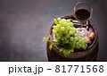 Red wine glass and white grape on old barrel 81771568