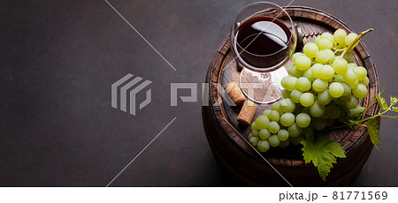 Red wine glass and white grape on old barrel 81771569