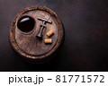 Red wine glass and vintage corkscrew on old barrel 81771572