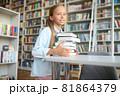 Calm pretty schoolchild putting the books on the table 81864379