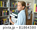 Tranquil pensive schoolchild with books looking away 81864380