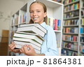 Joyous schoolchild with textbooks standing at the library 81864381