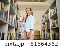 Pleased young schoolgirl posing for the camera at the library 81864382