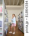 Serious cute schoolchild focused on choosing books 81864384