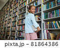 Pleased schoolchild with textbooks looking back over her shoulder 81864386