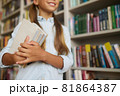 Happy schoolchild with books standing at the library 81864387