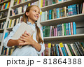 Joyous girl with textbooks in her hands at the library 81864388