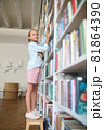Cute schoolchild posing for the camera at the library 81864390