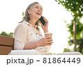 Joyful woman with coffee talking on smartphone 81864449
