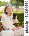 Woman in headphones showing smartphone screen 81864450