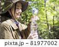 山でペットボトルの蓋を開ける若い女性 トレッキングイメージ 81977002