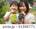 葡萄を持つ親子 81986771