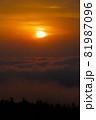 雲海の向こうからぼんやりと昇った太陽が雲の切れ間に差し掛かり光出す 81987096