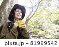 アウトドアチェアに座って飲み物を飲む女性 トレッキングイメージ 81999542