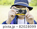 アウトドア用のデジカメを構える小学生女の子 トレッキングイメージ 82028099