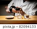 日本酒を料理人注ぐ 82094133