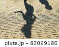 キックボードで遊ぶ二人の少女の長い影が動き出しそう 82099186