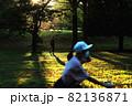 西陽さしこむ公園で手前に自転車の女子、遠くにウォーキングする男性 82136871