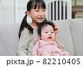 ソファに抱っこして座る赤ちゃんと幼児の仲良しの姉妹 82210405