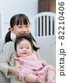 ソファに抱っこして座る赤ちゃんと幼児の仲良しの姉妹 82210406