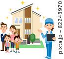 住宅の前に立つ家族と書類を手に持つ青い作業着の女性 82243970