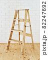 白いレンガの壁の前に置かれたアンティークな木製脚立 82247692