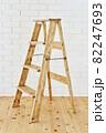 白いレンガの壁の前に置かれたアンティークな木製脚立 82247693