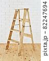 白いレンガの壁の前に置かれたアンティークな木製脚立 82247694