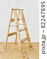 白いレンガの壁の前に置かれたアンティークな木製脚立 82247695