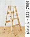 白いレンガの壁の前に置かれたアンティークな木製脚立 82247696