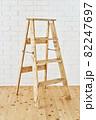 白いレンガの壁の前に置かれたアンティークな木製脚立 82247697