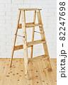 白いレンガの壁の前に置かれたアンティークな木製脚立 82247698