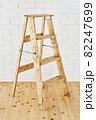 白いレンガの壁の前に置かれたアンティークな木製脚立 82247699