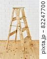 白いレンガの壁の前に置かれたアンティークな木製脚立 82247700