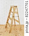 白いレンガの壁の前に置かれたアンティークな木製脚立 82247701